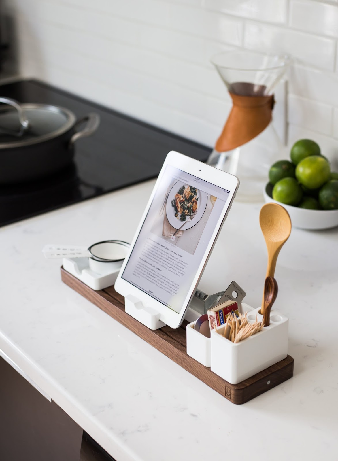 A recipe opened on a tab, placed on a stand on the kitchen counter