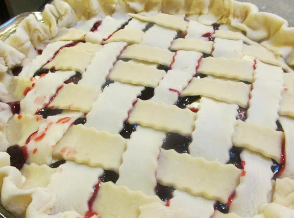 Seal strips underneath bottom crust, and flute edges with fingers. Brush top of pie...