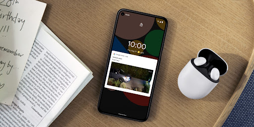 A phone sits on a sofa near a book.