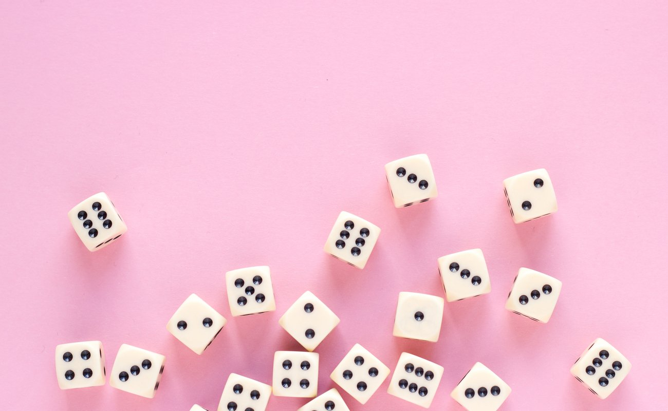 gaming dice with copy space on pink background