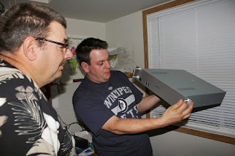 Photo: Garth holding the VE4WDR D-Star repeater with Glen looking on