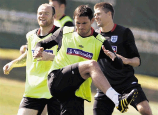 England's Frank Lampard (C) warms up with Wayne Rooney (L) and Steven Gerrard during a World Cup soccer training session at the Royal Bafokeng Sports Campus near Rustenburg June 21, 2010.  REUTERS/Darren Staples   (SOUTH AFRICA - Tags: SPORT SOCCER WORLD CUP)