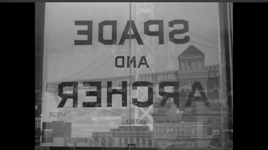 """Photo: Shot 5 of 18.  Duration: 12 seconds.  The first interior shot.  The Bay Bridge is visible through Spade and Arher's window.  The window is labeled--like the city.  For detective fiction readers,""""San Francisco"""" is synonymous with """"Sam Spade""""--and vice-versa.  The film signifies """"San Francisco"""" to signify """"Sam Spade,"""" and this shot collapses the heavy underlining of the real place (sometimes signified with very artificial images, as was the practice during the period), with the fictional universe of the famous detective."""