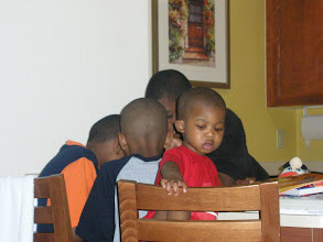 Photo: Miles, Kamau and my nephews Izjan and Alijzah huddled around an I Spy book.