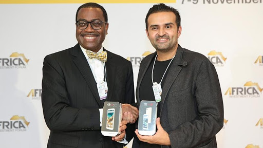 AfDB president Akinwumi Adesina and Mara Group founder Ashish Thakkar hold a replica of the new smartphone to be produced in SA. (Photo source: AfDB)