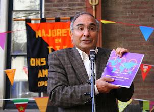 Photo: De Turkse schrijver en Jordaanbewoner met het eerste exemplaar van het buurtfotoboek 'Gezichten van een wereldbuurt'.