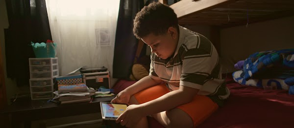 A child plays a game on a tablet in his bedroom
