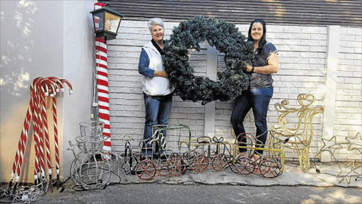 LIT UP: Lynda Gower, left, and Tamara Sutton Hartwanger sort through some of the many Christmas decorations being translocated. Picture: SUPPLIED