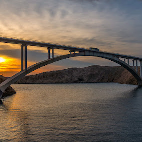 Pag Bridge by Tomaž Mikec - Buildings & Architecture Bridges & Suspended Structures ( water, famous place, bridge - man made structure, scenics, sea, travel, architecture, transportation, coastline, landscape, rock - object, sky, nature, blue, sunset, outdoors, river )