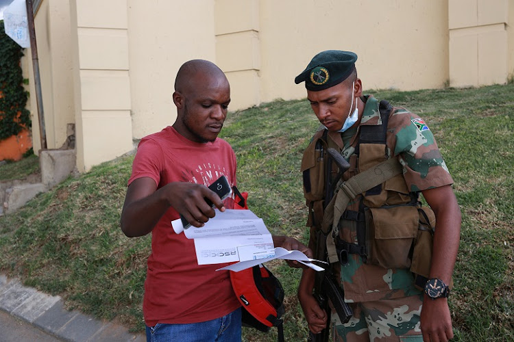 A SANDF soldiers checks the permits of a man who was at home during the country's lockdown on Friday.