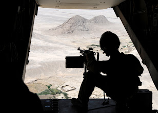 Photo: A U.S. Marine MV-22 Osprey aircrew member deployed to Helmand province, scans the terrain below during an Aug. 4 mission to support Marine Corps Gen. John R. Allen, commander of NATO and International Security Assistance Force troops in Afghanistan, during his Regional Command-Southwest battlefield circulation.  ISAF is a key component of the international community's engagement in Afghanistan, assisting Afghan authorities in providing security and stability while creating the conditions for reconstruction development.
