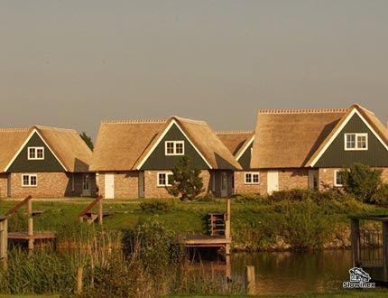 Zbiór małych domków z cegły z pokryciem trzcinowym nad kanałem wodnym