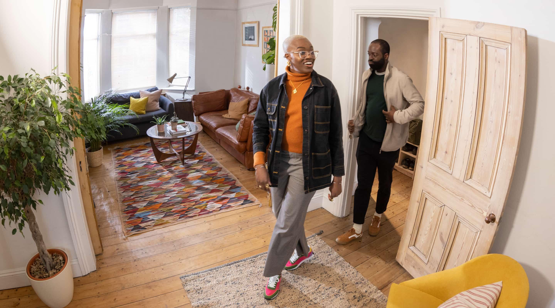 Una coppia entra nel salotto di un'abitazione.