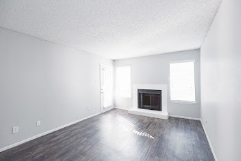 A3 floorplan's spacious living area with wood-style flooring and white brick fireplace