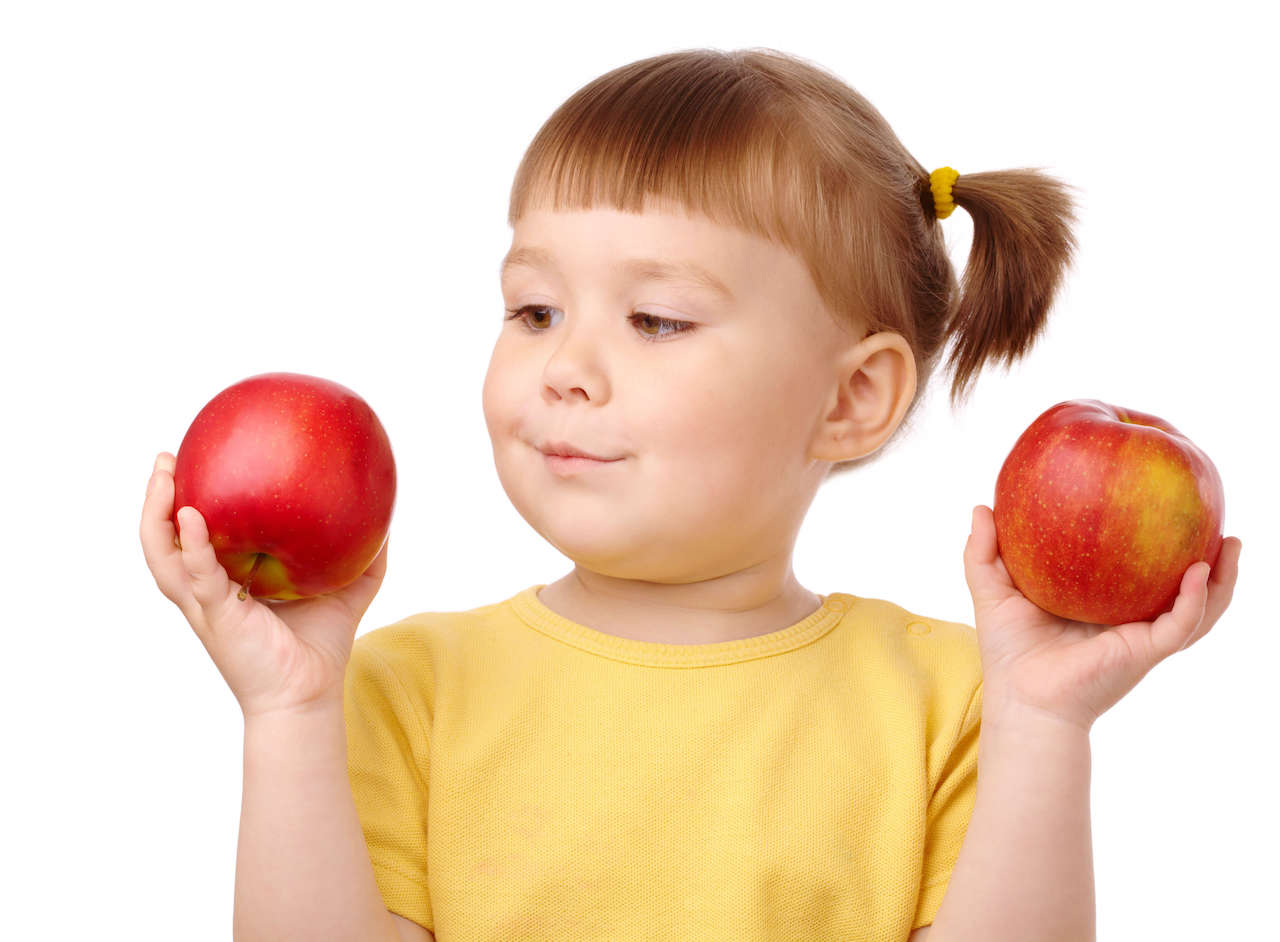 A kid holding two apples and choosing between them, similarly to the way that algorithms use conditionals to choose.