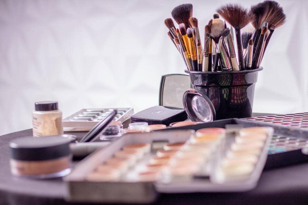 Una serie di prodotti per trucco e pennelli disposti su un tavoli