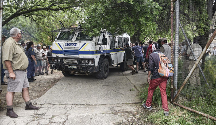 farmers snatch and pick at a Njala police vehicle outside the magistrate's office in Senekal where the killers of 21 year old farm manager Brendin Horner appeared at court on October 06, 2020 in Senekal, South Africa.