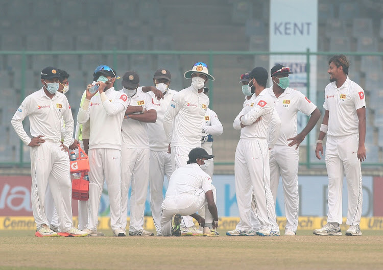 Sri Lanka players, wearing face masks, celebrate the dismissal of India's Ajinkya Rahane in New Delhi on December 5. Picture: REUTERS