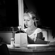 Photo: She sat there, in the streak of light, staring at her phone not paying attention at all to the world around her, and only from time to time licking her fingers melting ice ...  #monochrome #bwphotography #portraitphotography #portrait #LowKeyThursday