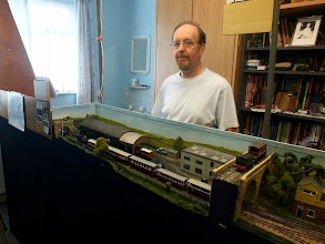 """Photo: 003 And here is Tim with half the layout (!) in his """"man cave"""" at home in 2013 which was the best that I remembered to manage in terms of a complete layout photo (note: must try harder in future). The main differences from 2012 are an improved backscene, some scenic additions and a few more """"exhibition battle honours"""" on the fiddle yard front screen to the left of the photo"""