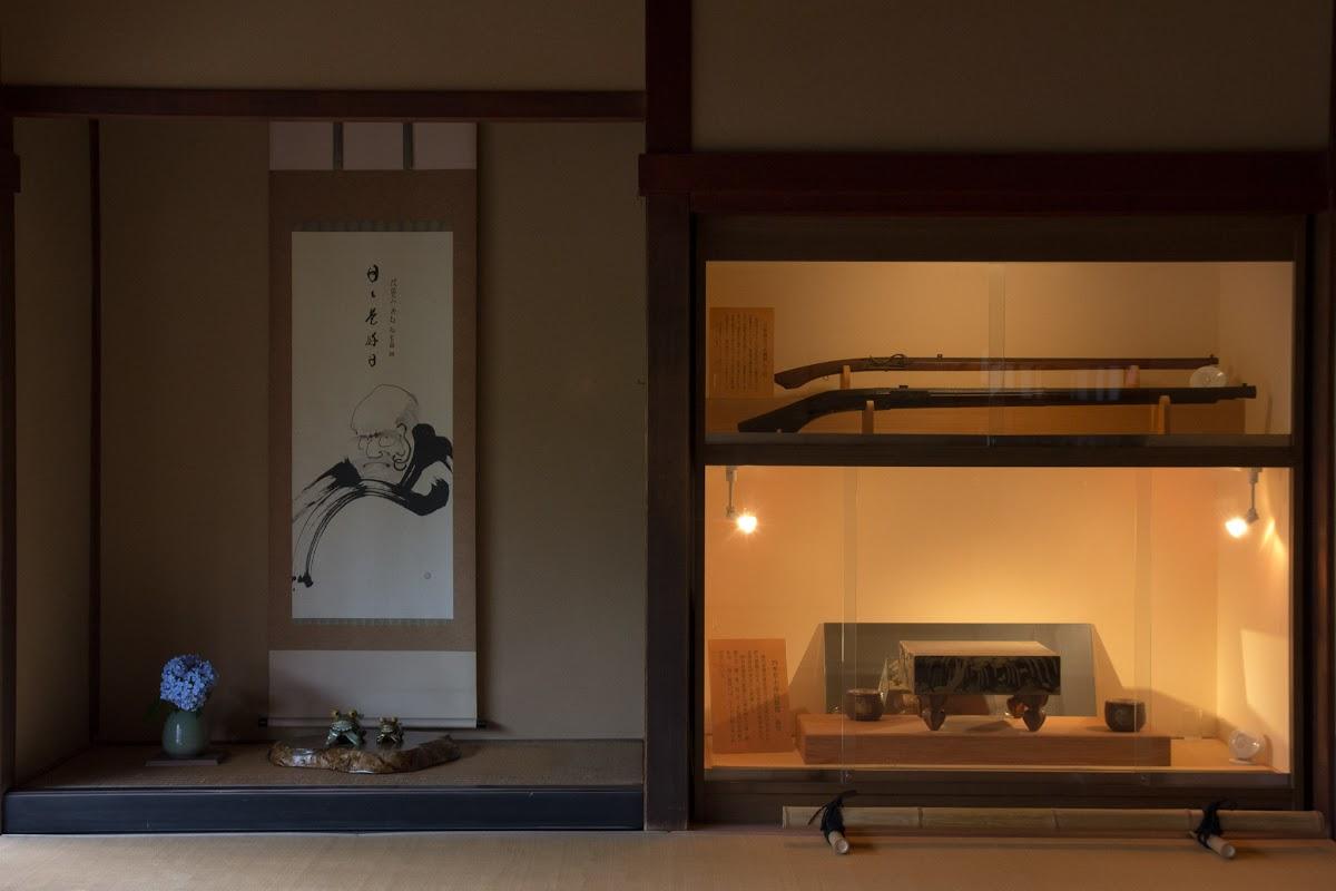 Daruma-Wandbild und Vitrine mit den Feuerwaffen und Go-Brett