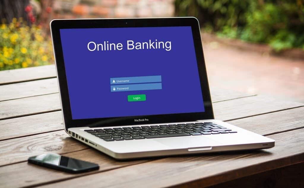 Notebook Aberto Em Uma Página De Banco Online E Com Um Celular Ao Lado.