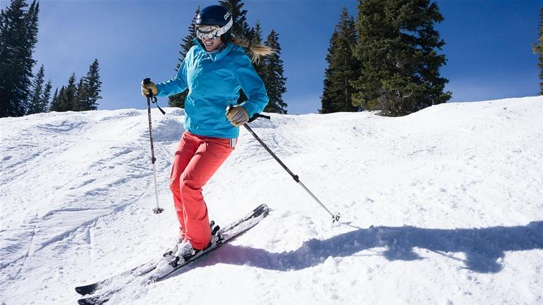 A person riding skis down a snow covered slope  Description automatically generated