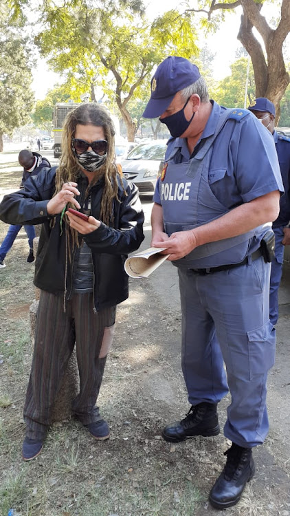 Byron Bernad, director of Human Rights Front of South Africa, speaks to a police officer outside the Union Buildings in Pretoria.