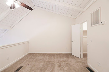 Loft with light carpet and walls and ceiling fan