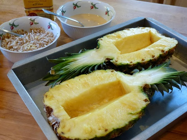 With a sharp knife slice the pineapple in hale with leaves intact. Cut the...