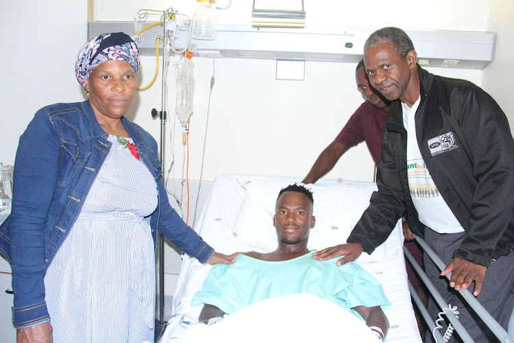 Triathlete Mhlengi Gwala in his hospital bed flanked by his mother, Fundi Magwaza, and KwaZulu-Natal MEC Sibongiseni Dhlomo.