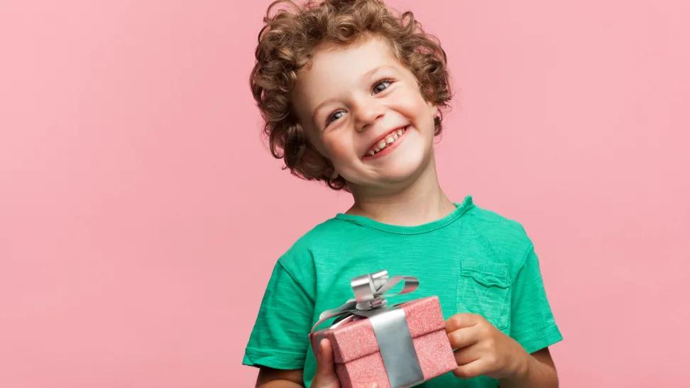 bé trai cười khi cầm hộp quà