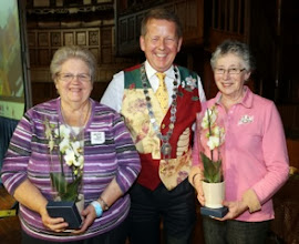 Photo: INIB Honey Show Secretary Madeline McMullan and Assistant Honey Show Secretary Vera Crawford receiving an orchid and paperweight from INIB President Bill Turnbull