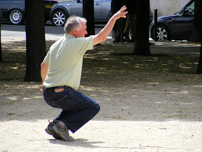 Photo: This player shows the tanque (pronounced tan-KAY) bent knee position favored by experienced throwers. This gives boules the name of petanque (pronounced peh-TANK) in the south of France in particular.