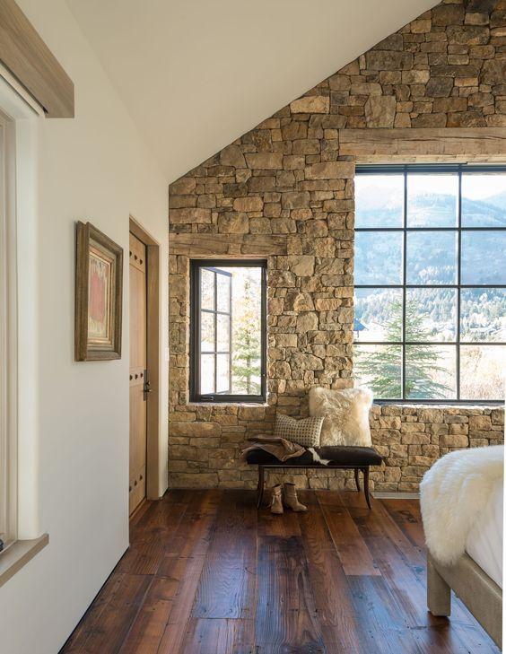 add a natural touch in a cabin bedroom with a stone accent wall