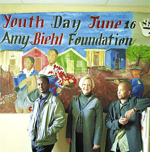 Outcomes: Linda Biehl, centre, with Ntobeko Peni, left, and Easy Nofemela, two of the men who killed her daughter Amy. In an act of poetic injustice, the anti-apartheid activist was stabbed and beaten in Gugulethu, Cape Town, because she was white. Her family went on to establish the Amy Biehl Foundation. Picture: SUPPLIED