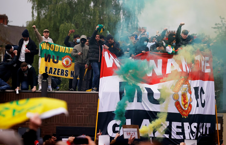 Manchester United fans holding banners and flares protest against the club's owners before the Premier League match between Manchester United and Liverpool at Old Trafford, Manchester, on May 2, 2021.