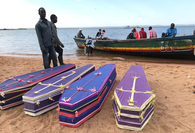 Volunteers arrange the coffins containing the dead bodies of passengers on September 22 2018. The bodies were retrieved after a ferry MV Nyerere overturned off the shores of Ukara Island in Lake Victoria, Tanzania.