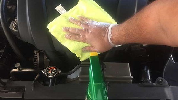 a man using a cloth to wash the car's engine