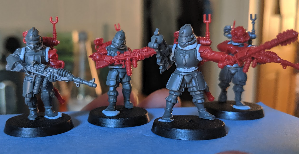 Four unpainted 28mm soldiers with bluetack holding them together