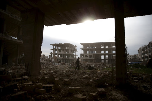 A man walks on the rubble of damaged buildings in the rebel-controlled area of Jobar, a suburb of Damascus, Syria. Picture: REUTERS