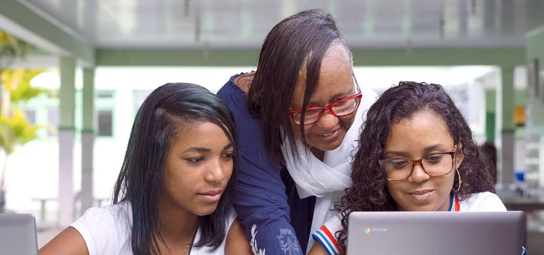 Desafio de inovação. Dois alunos trabalham em um Chromebook enquanto um professor se inclina.