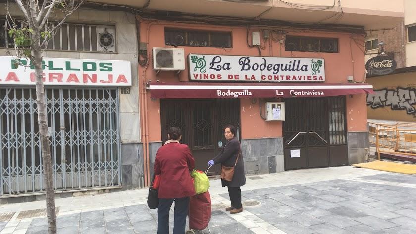 Dos señoras saludándose en la calle Trajano. Parecen estar poniéndose al día, cargadas de alimentos, frente a la Bodeguilla y Pollos La Granja.