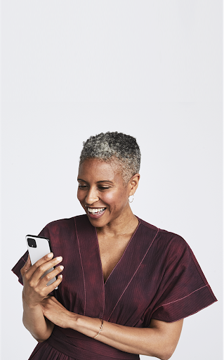 An image of a woman smiling as she holds her Google Pixel phone.