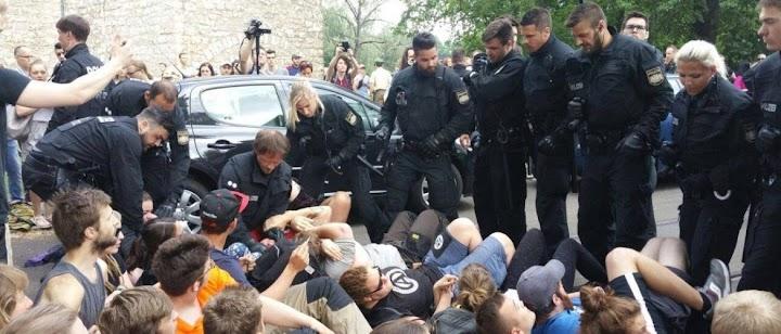 Protestierende Schüler am Boden liegend, drumherum Polizei, bemüht sie wegzutragen.