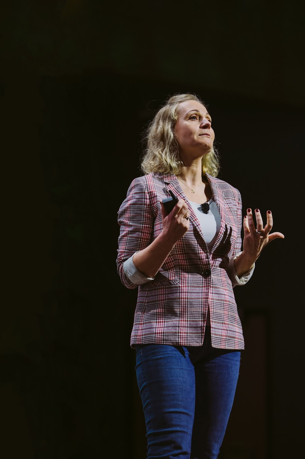 Woman standing on a stage,  giving a presentation at a Google for Startups event