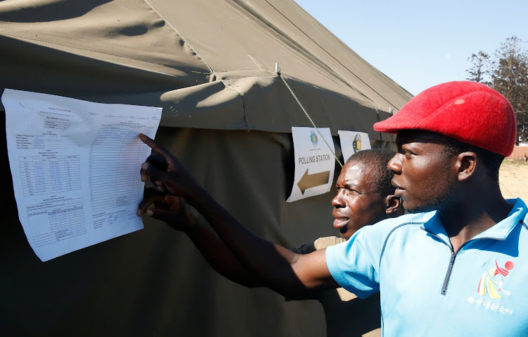 Residents of Mbare township examine uncollated results posted on a polling station following general elections in Harare, Zimbabwe, July 31, 2018.
