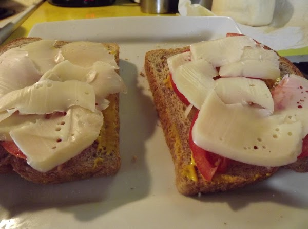 Drizzle mustard on all four slices of bread, then top with tomato slices and cheese...