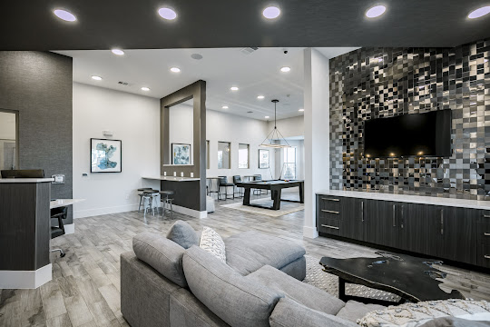 Clubhouse with wood-inspired flooring, lounge area with gray couch, and game area with billiards table