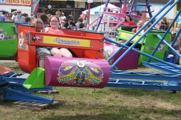 two young girls riding on a carnival roller coaster